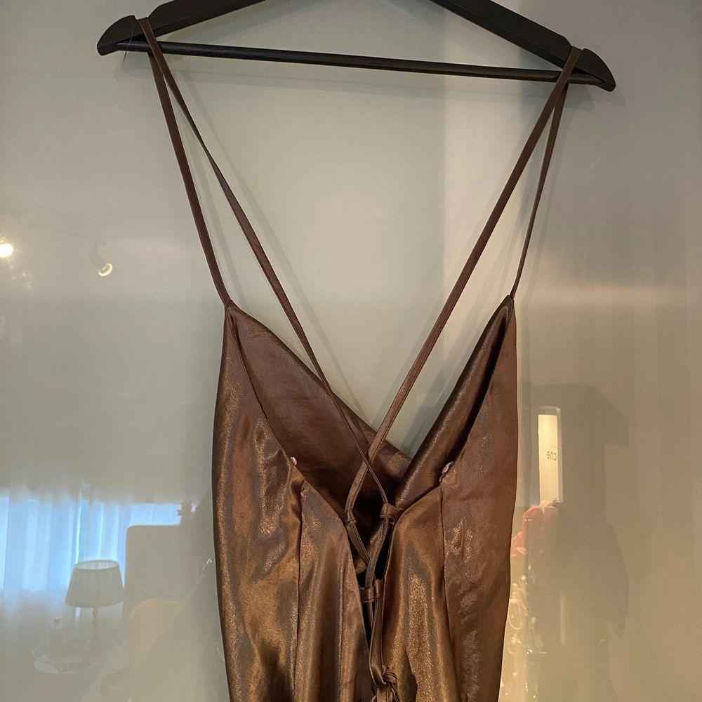 """Grön kort klänning i """"satin"""" från ASOS. Använd fåtal gånger. Knytning i ryggen som går att """"spänna åt"""". Size 42 (mindre i storlek).. Klänningar."""