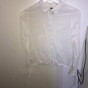 En somrig, vit skjorta i skönt bomullsmaterial. Går att öppna och stänga (beror lite på hur man själv vill styla den). Det finns även söta detaljer längs händerna.