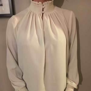 Feminin cremevit blus med hög krage och fina detaljer. Begagnat skick