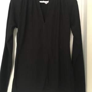 En svart v-ringad ribbad tröja. Man kan välja hur mycket v-ringning det ska vara. Och den är inte så stor som man tror. Köparen står för frakten, (pris kan diskuteras) och jag vet att kvaliteten på bilderna inte blev bra