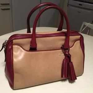 Elegant Coach beige/ röd läder handväska. Superfint och väldigt exklusivt och har många praktiska fack både med och utan gragkedja.Mått: 32cm x 25 cm x 17cm