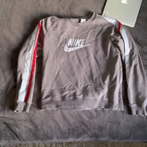 Grå tjocktröja från Nike med stripes på ärmarna. Riktning skön tröja med bra passform. Passar till nästintill allt och priset bestämd av köpare