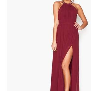 Lång klänning i en vinröd färg men jättefina detaljer och rygg. Använd en gång, storlek 38. Har sluta vid vänster ben. Jag står för frakt !!