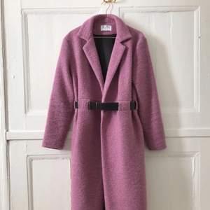 Rosa lång kappa. Från R/H Studio med svart läderbälte i midjan.
