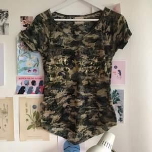 Fin tshirt från FAV med gulddetaljer, cirka storlek S.