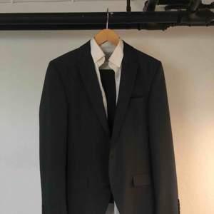 Slimmad Kostym, XS /39. På andra bilden är jag cirka 174 och väger 55. Mörkgrå kostym med byxor och vit skjorta.
