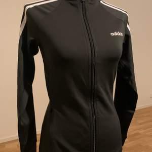 Oanvänd Adidas träningstopp. Storlek: XS men är ganska stor i storleken och kan därför passa upp till M