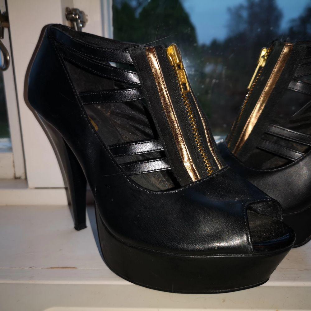 Bekväma och stabila klackar från din sko. Svart fakeläder med dragkedja och detaljer i guld. Platå 3 cm, klack 12 cm. Stl 37.. Skor.