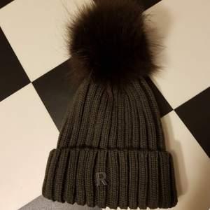 Från House of Saki  Oliver Night/greyish Stl: Onesize  Quality: Knit 70/30 70 % akryl 30% ull Päls: Tvättbjörn (Raccoon)  Finns inte att få tag på med den här tofsen längre. Inköpt Vintern 2018 men oanvänd. Kanonfin med snygg färg!  Dyr i inköp. Skickas med Postnord , då står du för frakten.