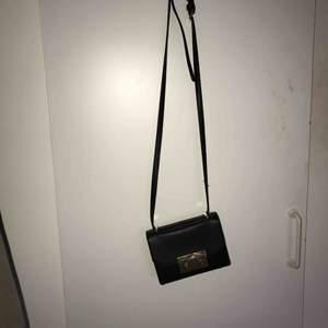 Svart handväska med gulddetaljer! Har en iPhone 7+ och den får plats. Köparen står för frakten