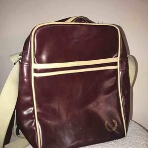 En fredperry väska, mörk röd. Skick: använt skick.