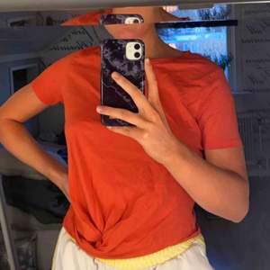 Lite kortare orange t-shirt med knytning i magen, aldrig använd (skrynklig pga legat i garderoben länge). Säljer eftersom jag har en liknande