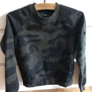 Camouflage färgad sweatshirt med ficka på armen. Nyskick endast provad