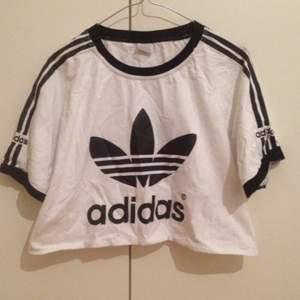Croppad adidas T-shirt i vitt med svart tryck.