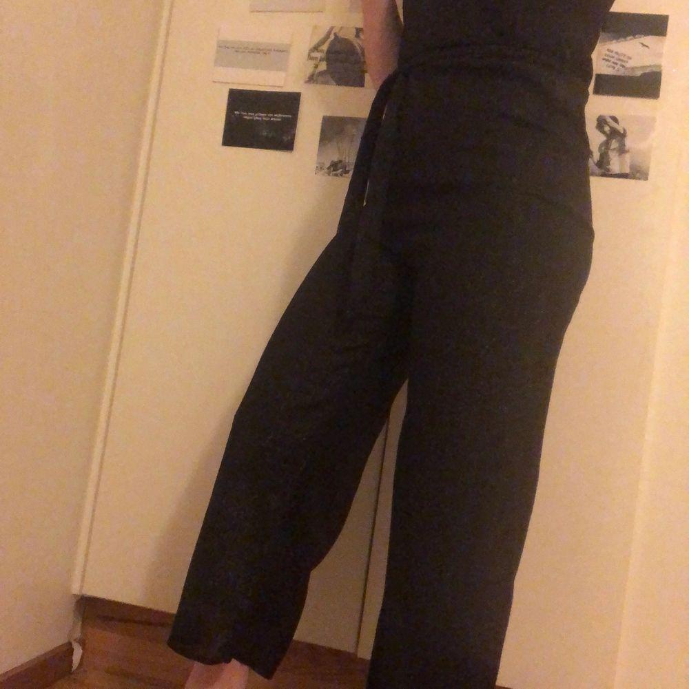 Svart lite glittrig jumpsuit med knytning i midjan från H&M i strl 34. Övrigt.