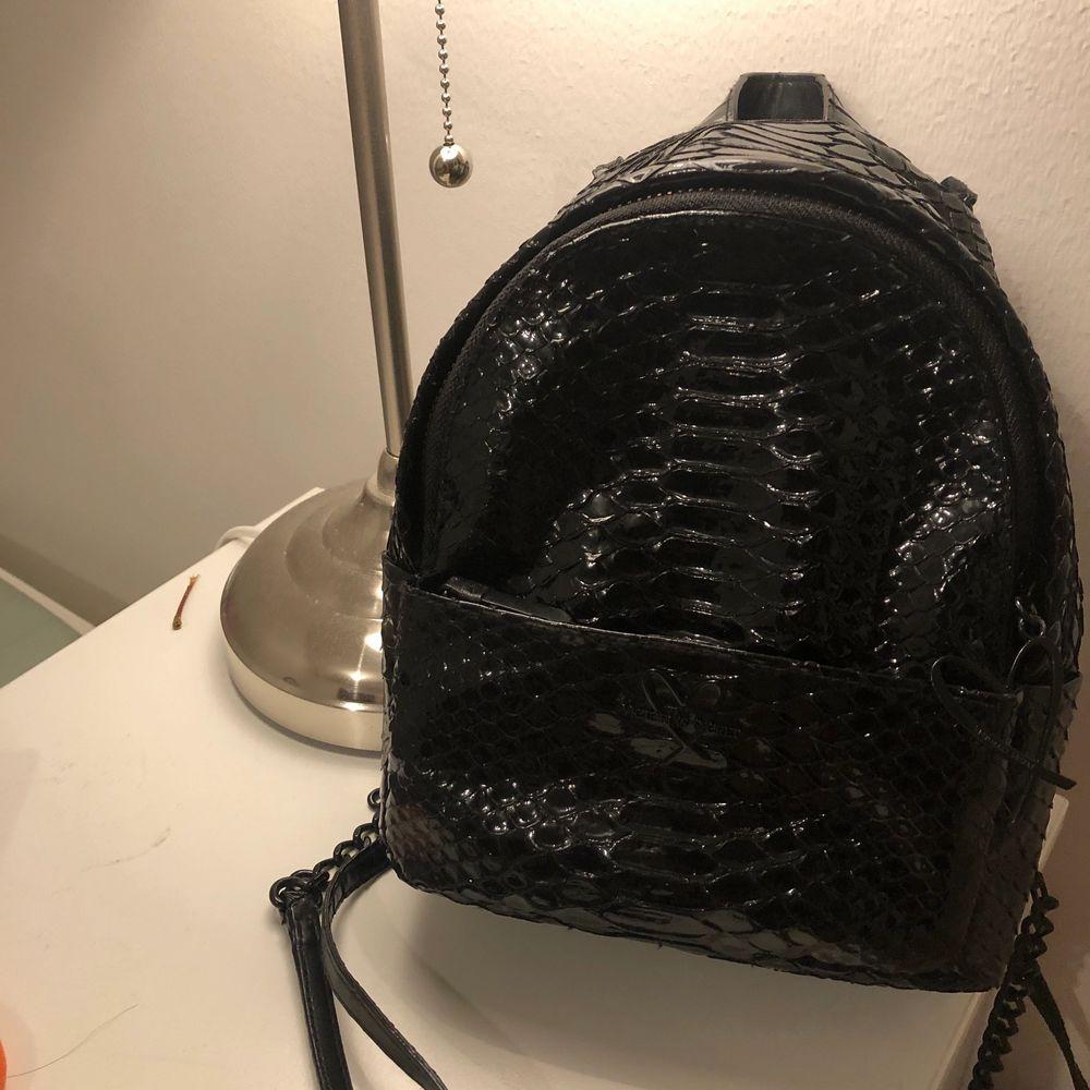 Säljer en felfritt svart Victorias Secret mini backpack. Rymmer en stor mobiltelefon, en plånbok samt en liten bok, (dessutom har en liten ficka som fungerar bäst för nycklar). Den är använd ett fåtal gånger, köpt för 1100kr. Kan skicka fler bilder. . Väskor.