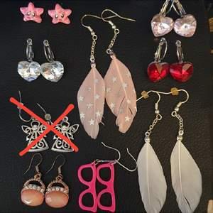 Olika örhängen, 15 kr/par. Från vänster till höger, uppifrån och ner: sjösjärnor, silvriga hjärtan, rosa handväskor, rosa fjädrar med silverstjärnor, rosa glasögon, rosa hjärtan, röda hjärtan, vita fjädrar. Rengörs självklart innan. Pris kan diskuteras. Skickas mot fraktkostnad.