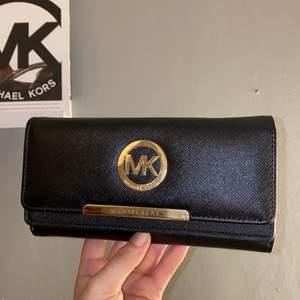 En skit snygg micheal kors plånbok i svart med guld. Vet inte om den är äkta eller inte då min mammas kompis köpte den som en present.