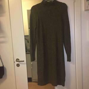 """""""Stickad""""klänning i mörkare grön färg med hög hals. Ungefär 150cm lång. 58% akryl, 22% bomull, 12% polyamid, 7% polyester och 1% elastan. Kan mötas upp alt. skicka."""
