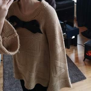 Stickad tröja ifrån märket Malene Birger. Beige med en mörkgrå rosett.