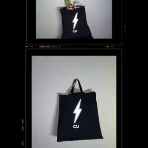 CU:s Inköpskasse 199 kr  ⚡️Produktinformation: En svart miljö-tygkasse i samma modell som en papperskasse med reflex detaljer på handtag och ett centrerat reflex motiv på kassen.  ⚡️Pitch: Med CU inköpskasse handlar du miljövänligt och billigare i affären samtidigt som  du syns i mörkret!   ⚡️Syfte: Den höjda plast skatten har resulterat i att ingen väljer att köpa dyra plastpåsar som dessutom skadar naturen längre när de handlar. Folk köper papperspåsar istället. Dessa har man inte lika stor användning för efter besöket i affären utan de blir liggande. Detta problem insåg alla vi i företaget CU samtidigt som vi arbetade med att ta fram reflex - tygpåsen till främst ungdomar. Därför har vi även skapat en tygpåse med en design i reflex i samma modell som en papperskasse. En modell som du lätt och smidigt kan packa ner dina varor i. Du sparar pengar,gynnar miljön,underlättar din vardag samtidigt som du gör dig sedd i trafiken på väg hem från t.ex affären sent på kvällen.