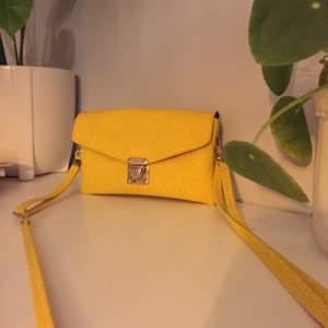 En gul väska. Den är mer guldig i färgen.
