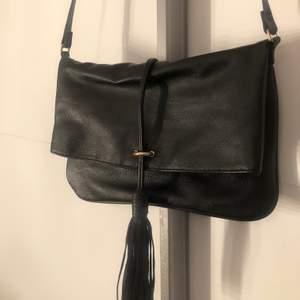 En svart liten axelbandsväska, köpt från h&m. Använd några gånger dock helt felfri.