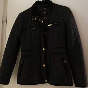 Quiltad jacka från MQ. Marinblå med svarta och guldiga detaljer