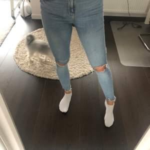 Stretchiga blåa jeans med slitningar, från Gina tricot storlek 40 sitter som en S/M