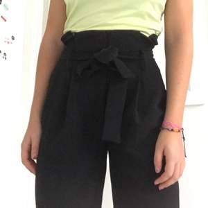 Högmidjade svarta kostymbyxor från Wera. Man knyter dem i midjan och de är extremt högmidjade med pösigare ben vilket ger en unik och smickrande siluett. Aldrig använda så i nyskick! De är i storlek 36 och relativt långa i benen, jag är 170 och de går över anklarna på mig.