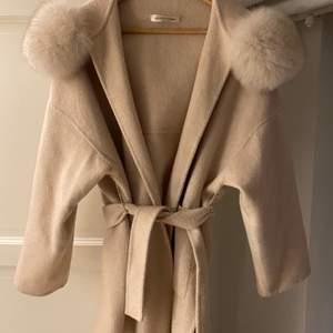 Beige kappa med fluffig pälsluva. Sparsamt använd. Storlek s men passar allt från xs-m . 50/50 ull och cashmere. Inköpt för 4500kr.