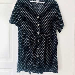 Kort smockad klänning från Asos. Svart med vita prickar och knappt hel vägen. Stl 36. Fint skick!  Köparen betalar frakten 44 kr