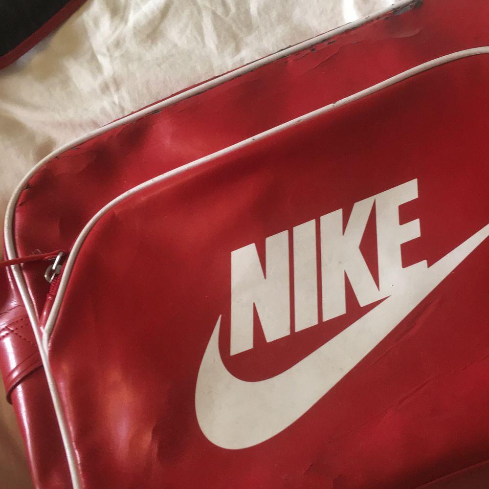 En röd, vintage, Nike axelväska❤️ Många fack, perfekt för träningen eller skolan! Mycket sprucken, men det inger patina tycker jag☺️ Den har fortfarande kvar att ge! . Väskor.