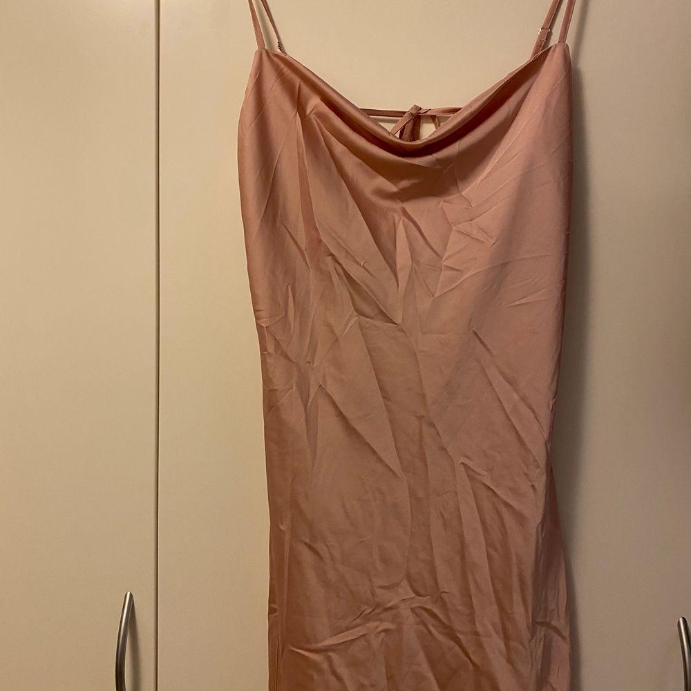Ljusrosa satinklänning i storlek 34, men även en 36 kan ha denna. Öppen rygg och snörning där också. Smala band som man även kan justera hur man vill ha dom. Den är aldrig använd, enbart provat den. Frakt tillkommer! . Klänningar.