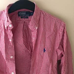 """En vit/röd rutig rherrskjorta från Polo Ralph Lauren. Storlek S, sitter lite oversized på mig som bär """"S dam"""". Köpt för 1250 kr, frakt ingår. Högstbudande får den om flera är vid intresse. Endast använd 1 gång!"""