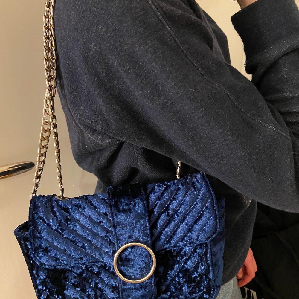 Säljer denna fina väska från Gina tricot som är i mörkblått sammet. Superfin färg som verkligen passar till ALLT. Knappen har dock gått sönder så den går inte att stänga. Frakt tillkommer, Hör av er om ni är intresserade💕. Accessoarer.