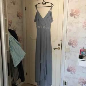 INTRESSEKOLL Superfin balklänning som jag inte tyvärr inte kommer få användning av igen.  Grå/blå färg med glitterbälte och slits. Lite lång på mig som är 166cm men är lätt att sy upp om man inte vill ha lite släp.