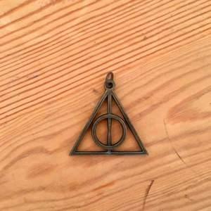 Berlock till halsband i form av dödsrelikernas symbol från Harry Potter. I bra skick, ca 5 cm högt.