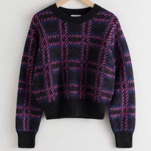 """Jättefin tröja i alpacka ull från &Other Stories. Den är med i en outfit på Netflix serien """"Emily in Paris"""" och är i bra skick. Den är svart med rosa och mörkblå linjer som skapar rutor. Storlek S men passar S/XS."""