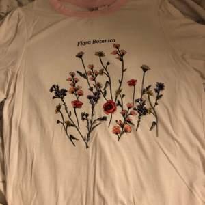 Vit t-shirt med ett blommigt tryck och rosa kanter i strl XS. Ganska stretchigt material. Skriv om du vill ha bättre bilder på plagget, tex passform på kroppen osv!
