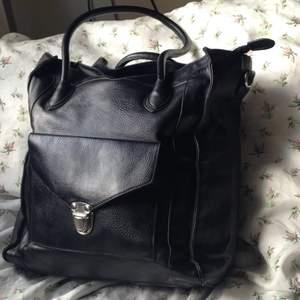 Svart handväska i faux läder.  Snygga detaljer. Silverfärgat spänne på facket på framsidan. Mycket rymlig. Innerfack med dragkedja. Tillhörande axelrem som går att haka fast (se bild 2). Dragkedja till stora facket (se bild 2).  Höjd: 33 cm Bredd: 29 cm Djup: 15,5 cm