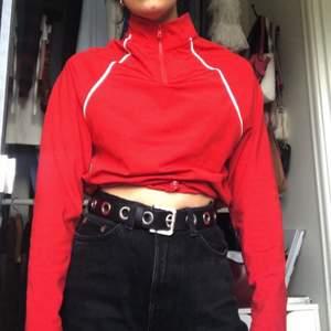 Trendig och sportig röd topp från ASOS Collusion, i storlek 34. Kan stylas på olika sätt med hjälp av dragskon som finns i tröjan!