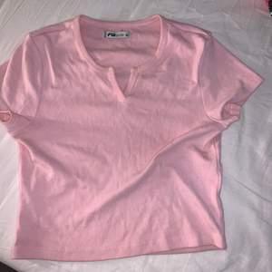 Rosa tshirt med en liten slits framtill. Sparsamt använd. Frakt tillkommer 💞