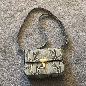 Ormmönstrad väska från glitter. Den är i bra skick och har ett axelband som man både kan ha kort och långt. Det finns en liten ficka inuti väskan med dragkedja. Väskans knäppe är i guld