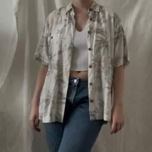 en tunn skjorta med snyggt mönster. träknappar som detalj vid knäppning och på ficka på bröstet. köpt secondhand men i nyskick!