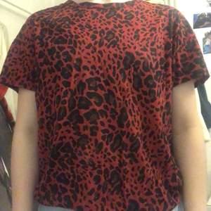 röd leopard mönstrad t-shirt från pull&bear. bra skick. lite annorlunda material men inget man märker så tydligt