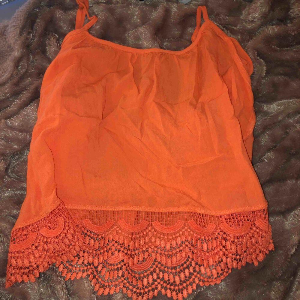 Ett linne isch men en ärm men inget tyg över axeln. Aprikos färg typ, detaljer längst ner . Toppar.
