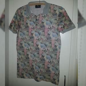 Piké tröja från Cedar wood state med pastell papegojor! Herrtröja men kan likaväl användas av kvinnor. Jag gillar den men får inte användning av den, i bra skick!