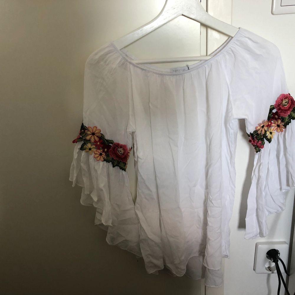 En vit off shoulder topp från Boohoo i väldigt skönt somrigt material. Den består av fina blommiga detaljer längs armbågarna. Säljes på grund av flytt. . Blusar.