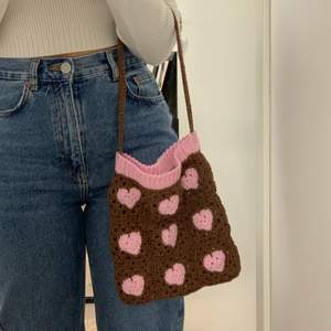 En brun väska med rosa hjärtan och ribbad kant som jag virkat själv! Väskans mått: 22 cm bredd, 25 cm längd